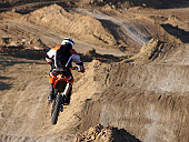A motocrosser hits the whoop-de-doos at the track in the late afternoon. Minor Photoshop work was done to remove logos and slightly alter the jersey for copyright purposes.