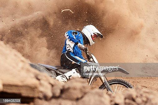Motocross biker taking a turn in the dirt.
