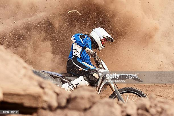 Motocross biker taking a turn in the dirt.