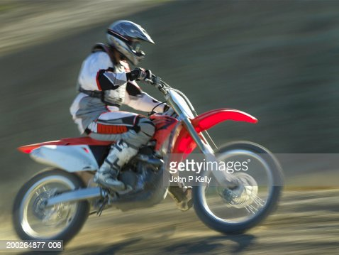 Motocross driver on dirt road, side view (blurred motion) : Stock Photo