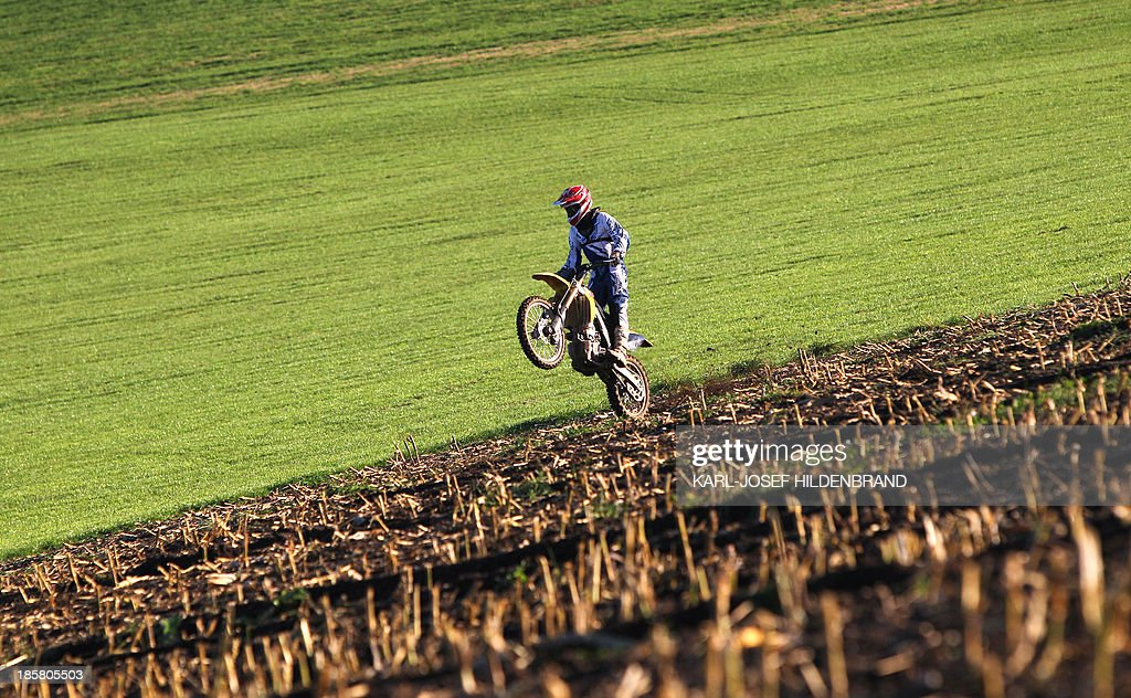 A motocross pilot practices on a harvested corn field near Kreen, southern Germany, on October 24, 2013.