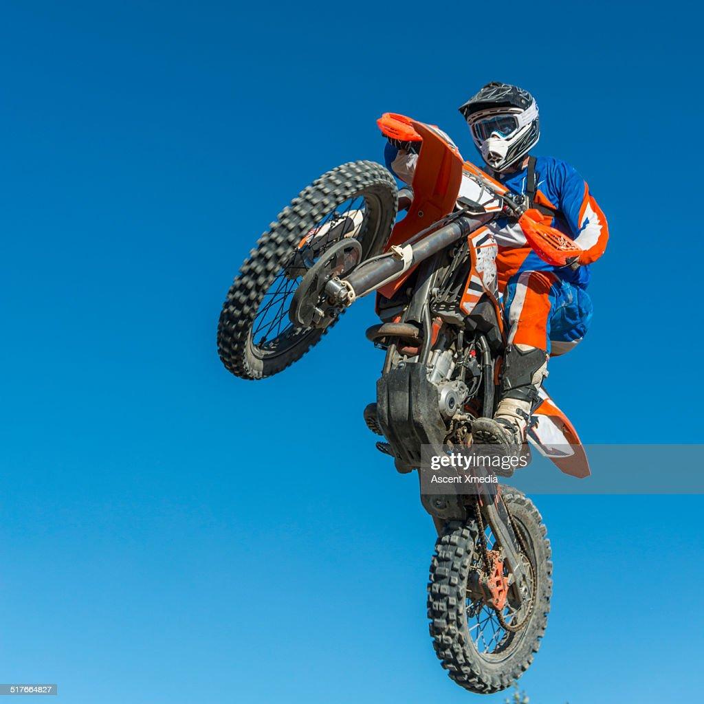 Motocross racer in mid air motion against blue sky