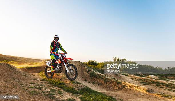 Motocross racer riding on dirt road and looking at camera.