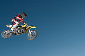 Motocross rider (11-13) in midair, low angle view