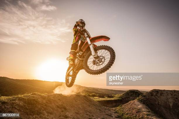 Motocross rider jumping over dirt hills at sunset.