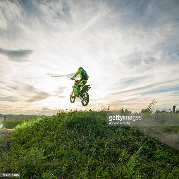 Motocross rider jumps grass hill on rural track
