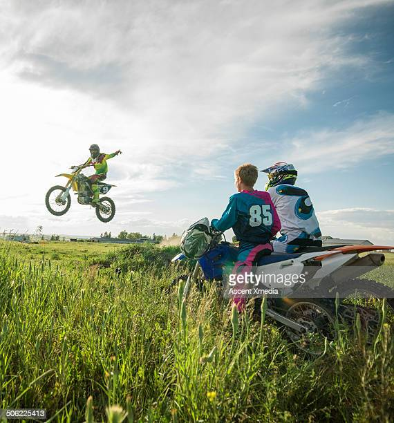 Motocross rider jumps while family looks on