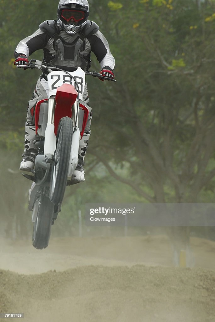 Motocross rider performing a jump on a motorcycle : Stock Photo
