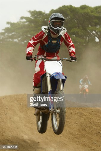 Motocross rider performing a jump on a motorcycle : Foto de stock