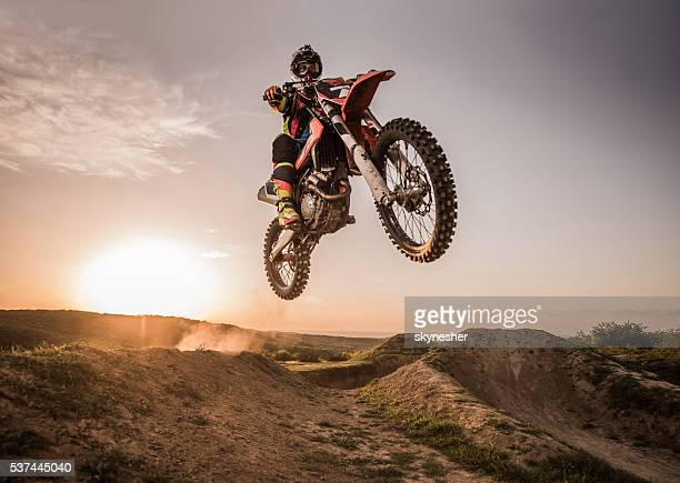 Motocross rider performing high jump at sunset.