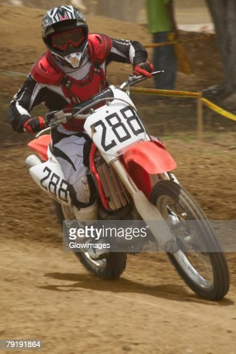 Motocross rider riding a motorcycle and leaning into a turn : Stock Photo