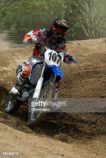 Motocross rider riding a motorcycle on a dirt road : Stock Photo