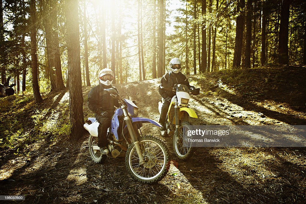 Motocross riders in forest sitting on bikes : Stock Photo