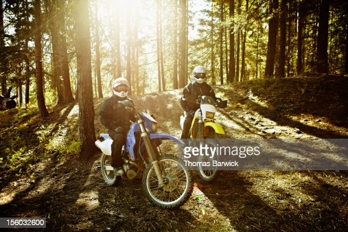 Motocross riders in forest sitting on bikes : Stockfoto