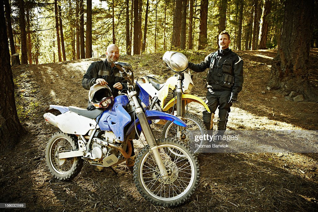Motocross riders next to bikes in forest : Stock Photo