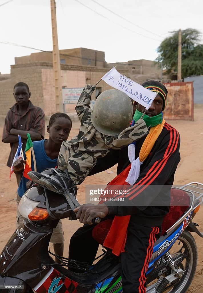 A motocyclist displays a doll wearing a military uniform and a sign reading 'Thank you F. Hollande' as Malian and French soldiers entered the historic city of Timbuktu, occupied for 10 months by Islamists who imposed a harsh form of sharia, on January 28, 2013. Hundreds of people scrambled Monday to give French-led troops a hero's welcome as they entered the city.
