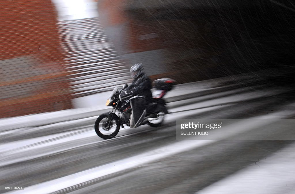 A motocyclist rides as snow falls in Istanbul on January 8, 2013. Heavy snowfall blanketed Turkey's commercial hub Istanbul, a city of 15 million, paralysing daily life, disrupting air traffic and land transport. Officials said the snow is expected to continue until late tomorrow, according to the weather forecast.
