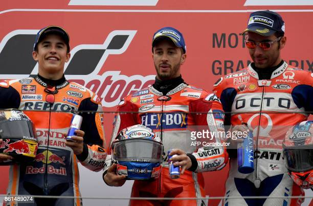 MotoGP class winner Ducati rider Andrea Dovizioso of Italy poses on the podium with second placed Honda rider Marc Marquez of Spain and third placed...