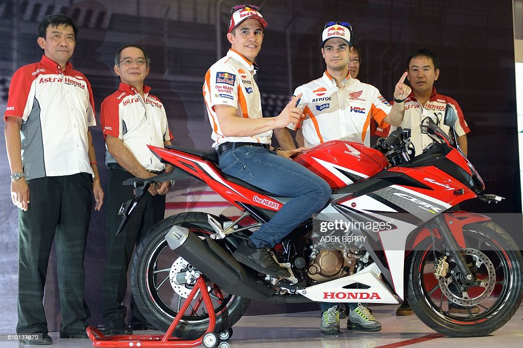 MotoGP motorcycle riders Marc Marquez (C-on bike) and Dani Pedrosa (2nd R) of Spain gesture as they attend the launch of the new Honda CBF150R bike at the Sentul International Circuit in Bogor on February 14, 2016. AFP PHOTO / ADEK BERRY / AFP / ADEK BERRY