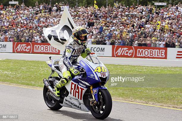 MotoGP world champion Valentino Rossi of Italy celebrates his 100th grand prix victory from pole position at the Dutch TT race at Assen on June 27...