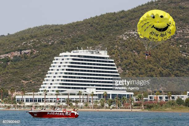 A motor boat pulls parasailing tourists in Izmir Turkey on July 25 2017 In Summer's extreme hot days people try to cool themselves off with various...