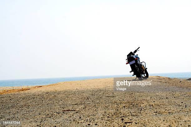 A motor cycle parked at a sea shore