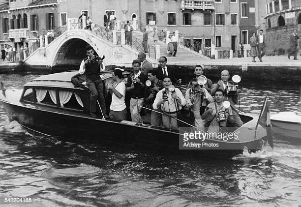 A motor launch filled with photographers following actress Brigitte Bardot and singer Sacha Distel down the canal during the Venice Film Festival...