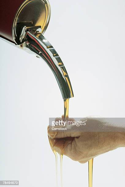 Motor oil pouring over hand
