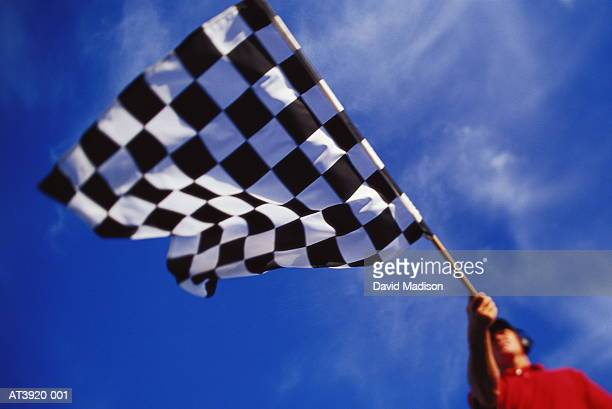 Motor racing official waving chequered flag, low angle view
