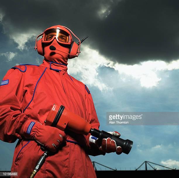Motor racing pit crew member holding airgun