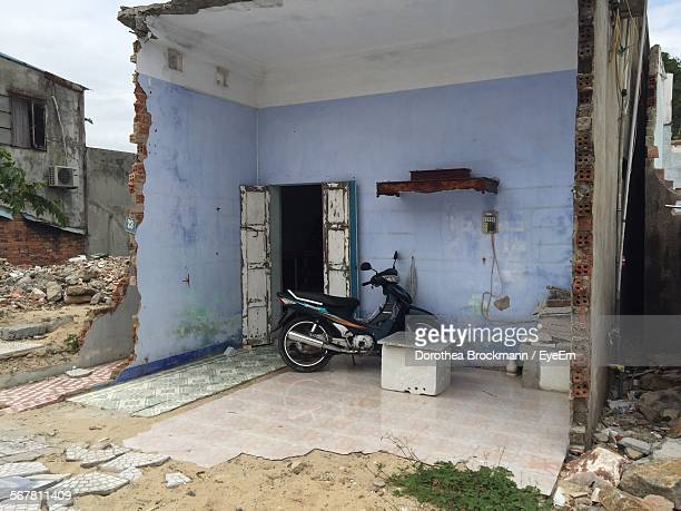 Motor Scooter Parked In Broken House