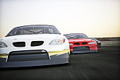 Front view of auto racing race cars racing on a track with motion blur.