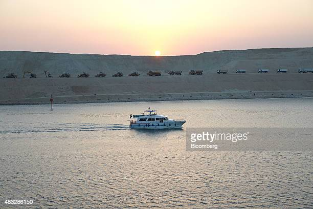 A motor vessel passes through a section of the New Suez Canal operated by the Suez Canal Authority as the sun sets in Ismailia Egypt on Thursday Aug...