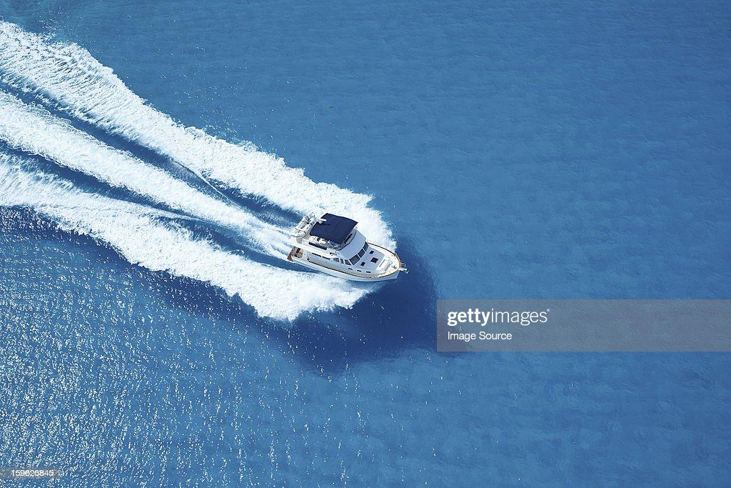Motor yacht ploughing across blue sea