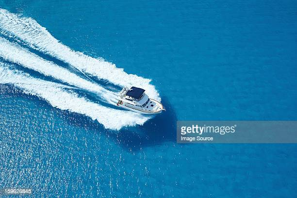 Motor yacht ploughing across blue sea