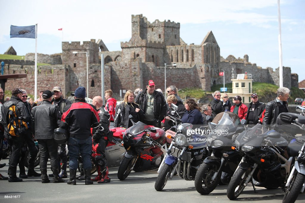 Motorbike fans gather along the promenade with Peel castle in the background on June 7, 2009 in Peel, Isle Of Man. The annual TT race is one of the highlights of the motorbike racing calender with fans travelling from around the globe to watch riders compete in the 37 and three quarter mile lap exceeding speeds of 200mph.