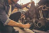 Attractive man is repairing a motorcycle in the repair shop