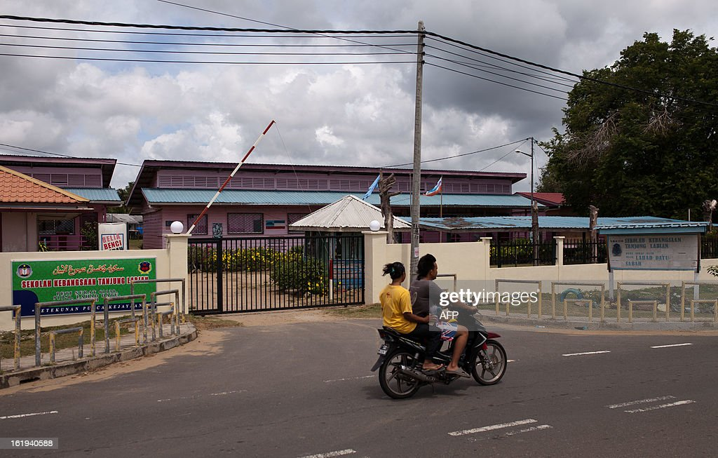 A motorbike rides past a closed primary school in Tanjung Labian, in the areas where suspected Philippine militants are holding off near Lahad Datu on the Malaysian island of Borneo on February 18, 2013. Followers of a Philippine sultan who crossed to the Malaysian state of Sabah this month will not leave and are reclaiming the area as their ancestral territory, the sultan said on February 17 amid a tense standoff.