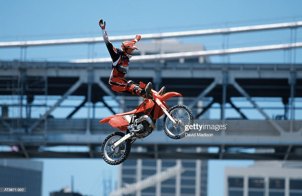 Motorbike stunt rider in mid-air, low angle view (Enhancement) : Stock Photo