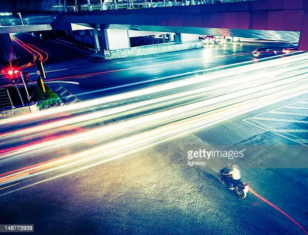 Motorbiker at an intesection in Bangkok.