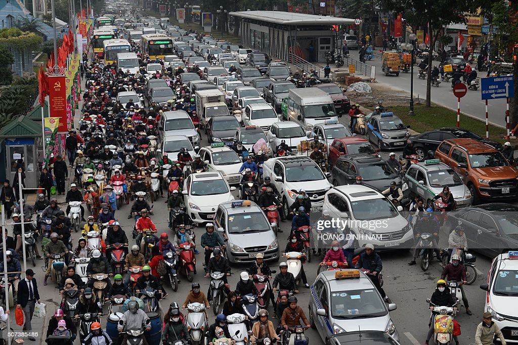 Motorbikes try to weave their way between the cars as they all fight for space on the road as heavy traffic clogs up a main street in downtown Hanoi...