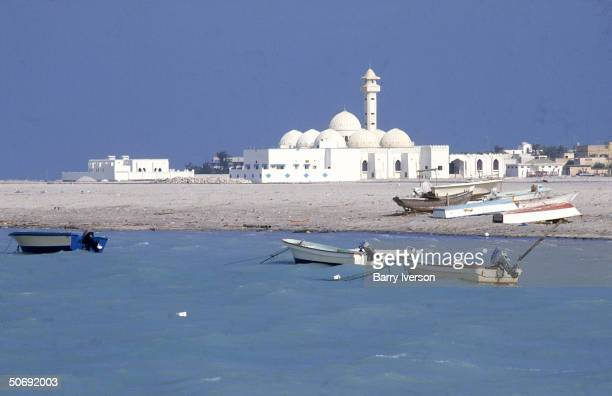 Motorboats off shore and cityscape w mosque of Persian Gulf port