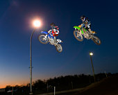 Motorcross riders jumping dirt bikes