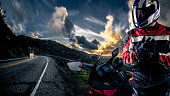 Male motorcyclist wearing protective leather racing suit with a red bike or motorcycle on an open road.  The image is shot in HDR and composite.  The vehicle is cropped to become generic non branded.