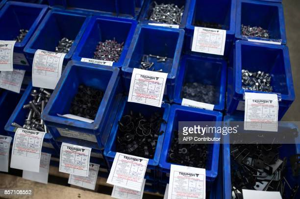 Motorcycle components are stored in containers adjacent to the assembly line at the Triumph Motorcycles factory in Hinckley central England on...