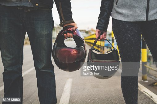 Motorcycle couple holding helmets in hands : Stock Photo