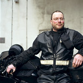 Motorcycle courier leaning against bike, portrait