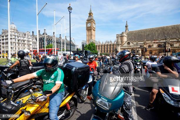 Motorcycle delivery drivers and motorcyclists take part in a demonstration in Parliament Square in central London on July 18 following a spate of...