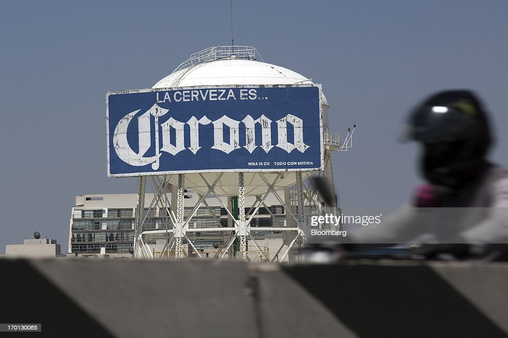 A motorcycle drives past a Corona sign atop the Grupo Modelo SAB brewery in Mexico City, Mexico, on Thursday, June 6, 2013. Heineken NV and Grupo Modelo SAB, the dominant brewers in Mexico with brands such as Dos Equis and Corona, are nearing the end of an almost three-year-old government antitrust probe. Photographer: Susana Gonzalez/Bloomberg via Getty Images