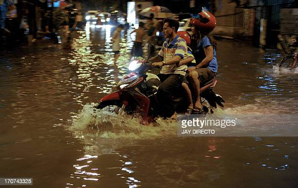 A motorcycle drives through floodwater in Manila on June 17 2013 The Philippine Atmospheric Geophysical and Astronomical Services Administration is...